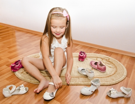 Cute little girl  puts her shoes at home
