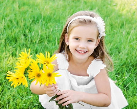 Cute little girl on the meadow with flower in summer day