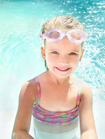 Cute smiling little girl in swimming pool in glasses photo