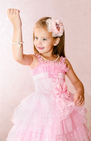 Portrait of adorable smiling little girl in princess dress look at the bracelet photo
