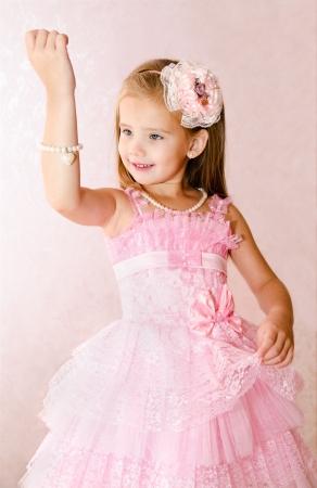 Portrait of adorable smiling little girl in princess dress look at the bracelet
