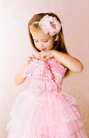 Portrait of adorable little girl in princess dress  looking for something in her handbag photo