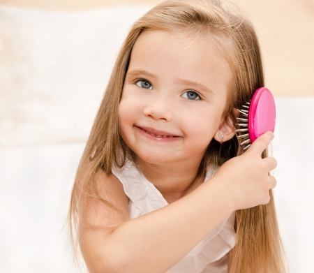 Portrait of smiling little girl brushing her hair closeup photo