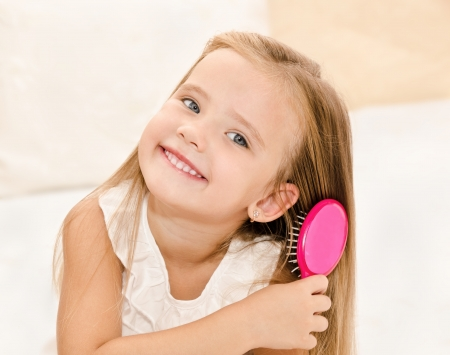 Portrait of smiling little girl brushing her hair closeup Stock Photo