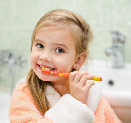tooth brush: Smiling little girl brushing teeth in bath