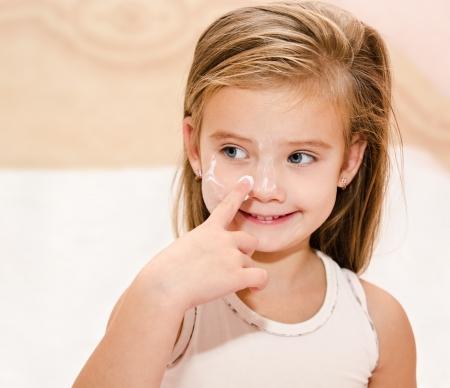 Cute smiling little girl  applying cream