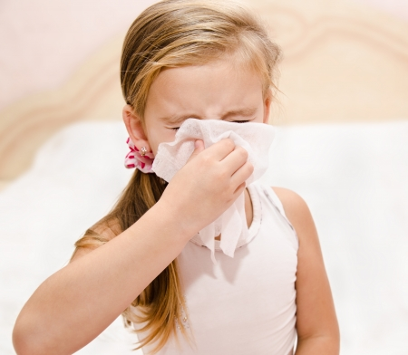 Little girl blowing her nose in a great effort closeup