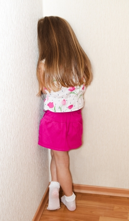 disobedient child: Naughty little girl is standing in the corner at home Stock Photo