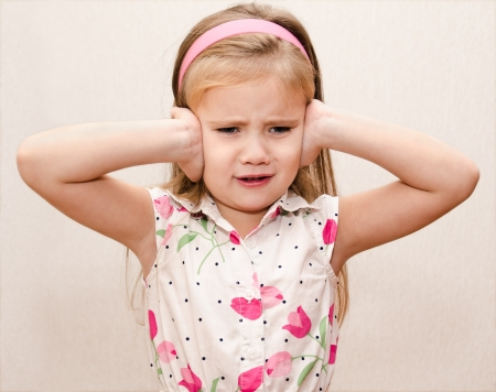 Disappointed little girl covering her ears photo