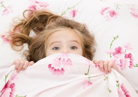 Little girl having childhood nightmares and fears hiding under the quilt Imagens - 23308257