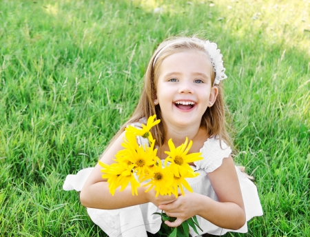 Cute happy little girl on the meadow with flower in summer day 免版税图像