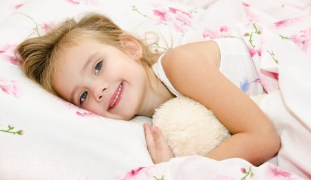 yoy: Cute smiling little girl waked up in her bed with toy Stock Photo