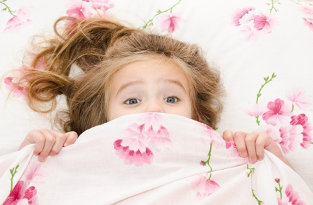 fear child: Little girl having childhood nightmares and fears hiding under the quilt