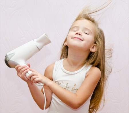 Cute smiling Little girl dries hair isolated Imagens