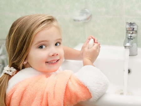 Smiling cute little girl washing hands in bathroom  photo