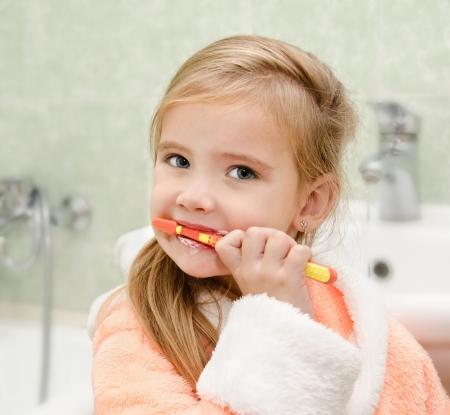 Glimlachend schattig klein meisje tandenpoetsen in bad Stockfoto