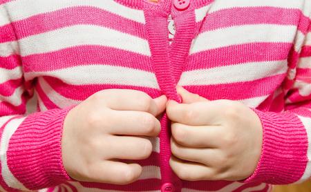 buttoning: Little girl buttoning her jacket closeup