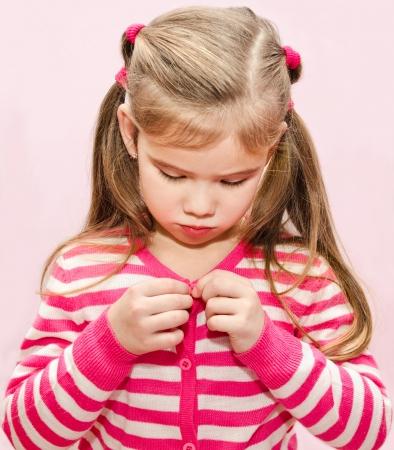 buttoning: Cute little girl buttoning her jacket closeup