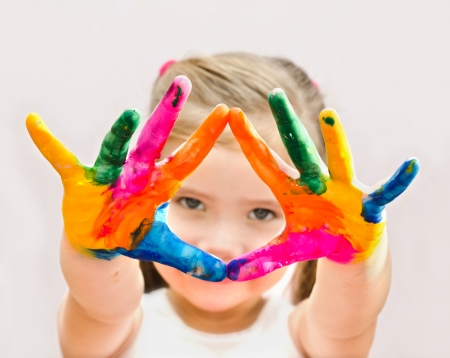 Cute little girl with hands in paint isolated
