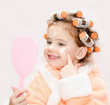 bath robes: Happy cute little girl in hair curlers with mirror applying cream isolated on a white