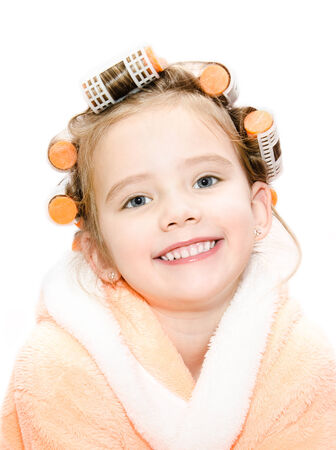Portrait of smiling cute little girl in hair curlers and bathrobe isolated on a white background  photo