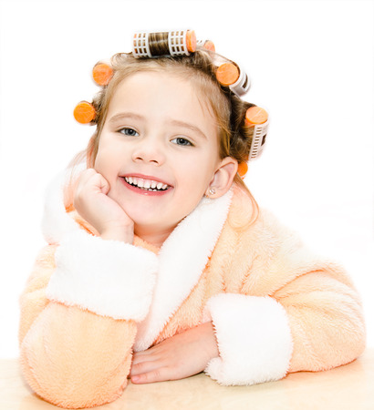 Happy cute little girl in hair curlers and bathrobe isolated on a white background  photo