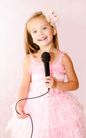 Beautiful little girl with microphone in princess dress isolated  Stock Photo