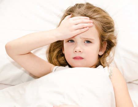 Sick little girl lying in the bed Imagens