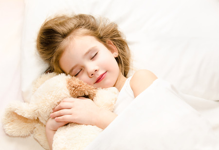 white bed: Adorable little girl sleeping in the bed with her toy