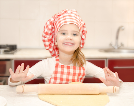 Smiling little girl with chef hat rolling dough in the kitchen  photo