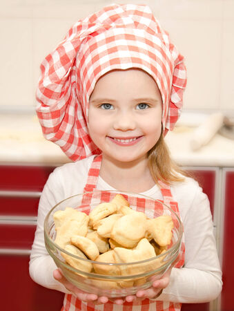 little table: Smiling little girl in chef hat holding bowl with cookies in the kitchen