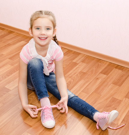 Cute smiling little girl tying her shoes at home