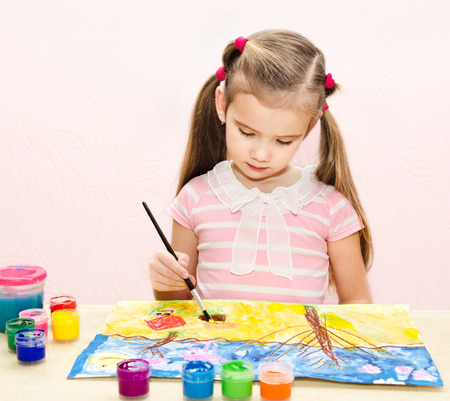 Cute little girl drawing with paint and paintbrush at home Stock Photo