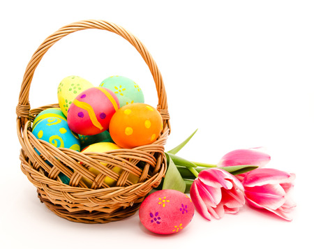 Colorful easter eggs in basket and flowers isolated on a white background photo