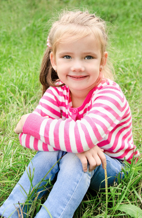 outumn: Portrait of adorable smiling little girl sitting on grass outdoor