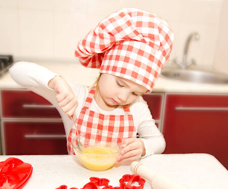 Little girl with chef hat stirrring cookie dough in the kitchen photo