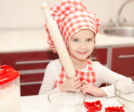 Smiling little girl with chef hat preparing to cook in the kitchen  photo