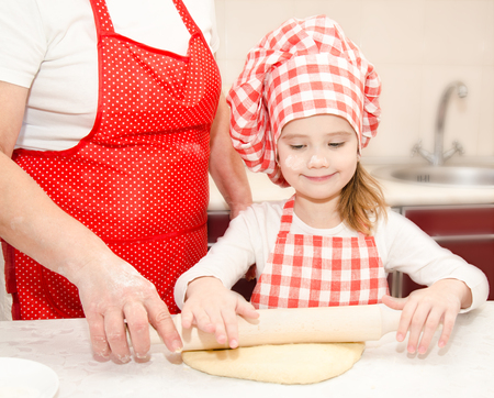 Little girl and grandmother rolling dough for cookies in kitchen photo