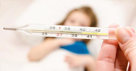 ragazza malata: Madre che tiene termometro primo piano e malati bambina a letto