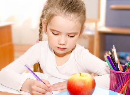 orthography: Cute little girl is writing at the desk  in preschool