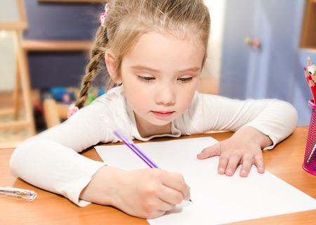 Cute little girl is writing at the desk  in preschool