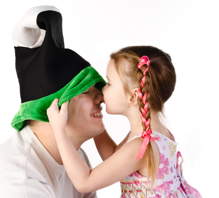 Little girl kissing her father in funny cap isolated on a white