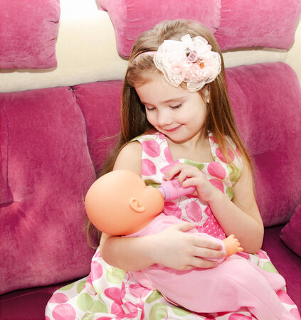 Cute smiling little girl playing with a doll at home photo