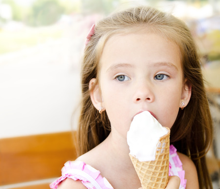 Thoughtful little girl eating ice cream outdoor photo