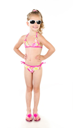 Cute smiling little girl in swimsuit and sunglasses isolated on a white photo