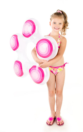 Cute smiling little girl in swimsuit with inflatable rubber ring isolated on a white Stock Photo