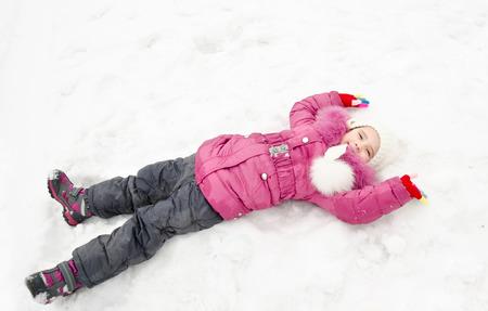 winterwear: Cute smiling little girl lying on snow in winter day outdoor