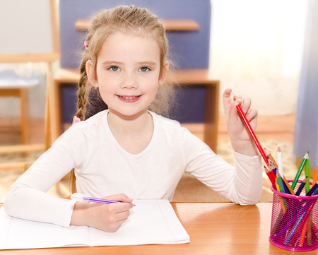 orthography: Cute smiling little girl is writing at the desk  in preschool Stock Photo