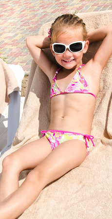 Smiling little girl lying on a chaise lounge and sunbathing photo