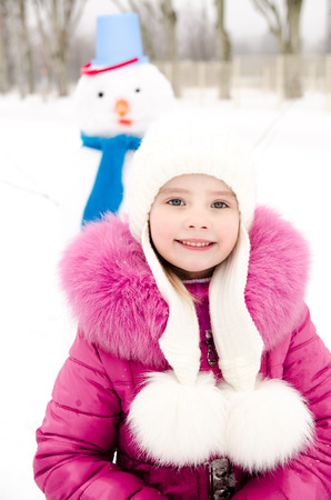 Portrait of smiling little girl with snowman in winter day outdoor photo
